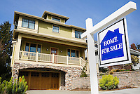 """Home with a """"for Sale"""" sign in front of it."""