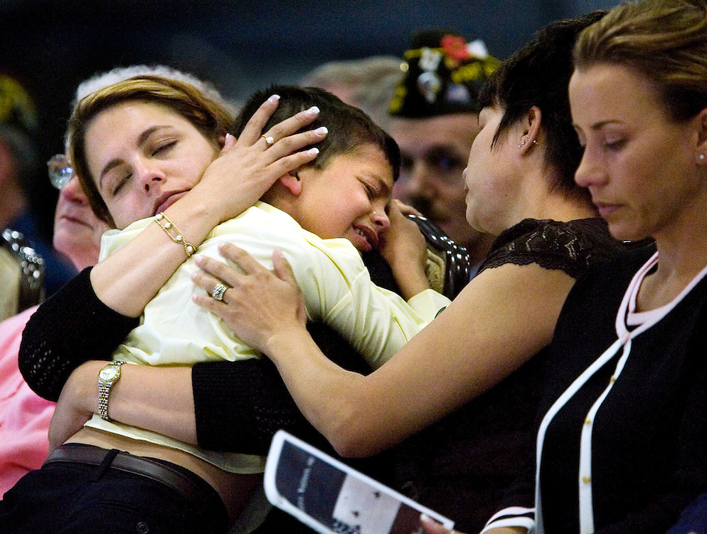 Danielle Balmer, left and her sister Angie Makin, right comforts Danielle son Anthony during the memorial service for their husband and father Special Agent Ryan A. Balmer, who was killed by a roadside bomb in Iraq, at Hill AFB , Utah June 8, 2007.  August Miller/ Deseret Morning News