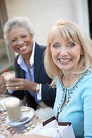 Smiling Women sitting Having Coffee Drinks