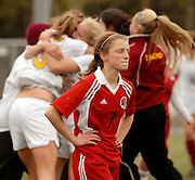 Juneau Douglas' Gretchen Dierking walks off the field as Dimond teammates celebrate after their 2-0 win Saturday afternoon during the state tournament finals at Anchorage Football Stadium.