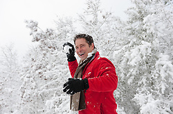 handsome man outdoors in the snow enjoying a snowball fight in the woods
