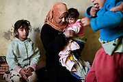 Zakhia, 3, is crying in the arms of her mother (centre) while Jasim, 5, (right) is playing with his father, in Fallujah, Iraq. Both children are suffering from severe neurological disorders, and were born after the 2004 US-led battles for the city. Sausaan, (left) the family's healthy 8-year-old sister, born before the attacks, regularly assists her two disabled siblings. The parents and their relatives have no history of birth defects.