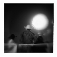 USA, Arizona, Holbrook, Blurred black and white image of rodeo fans watching fireworks display during small town celebration