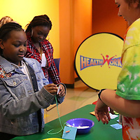 Baylee Hallmark,right, helps Ke'Asia Standifer, 11, make a Healthworks necklace Saturday at Healthwork's 9th Birthday celebration