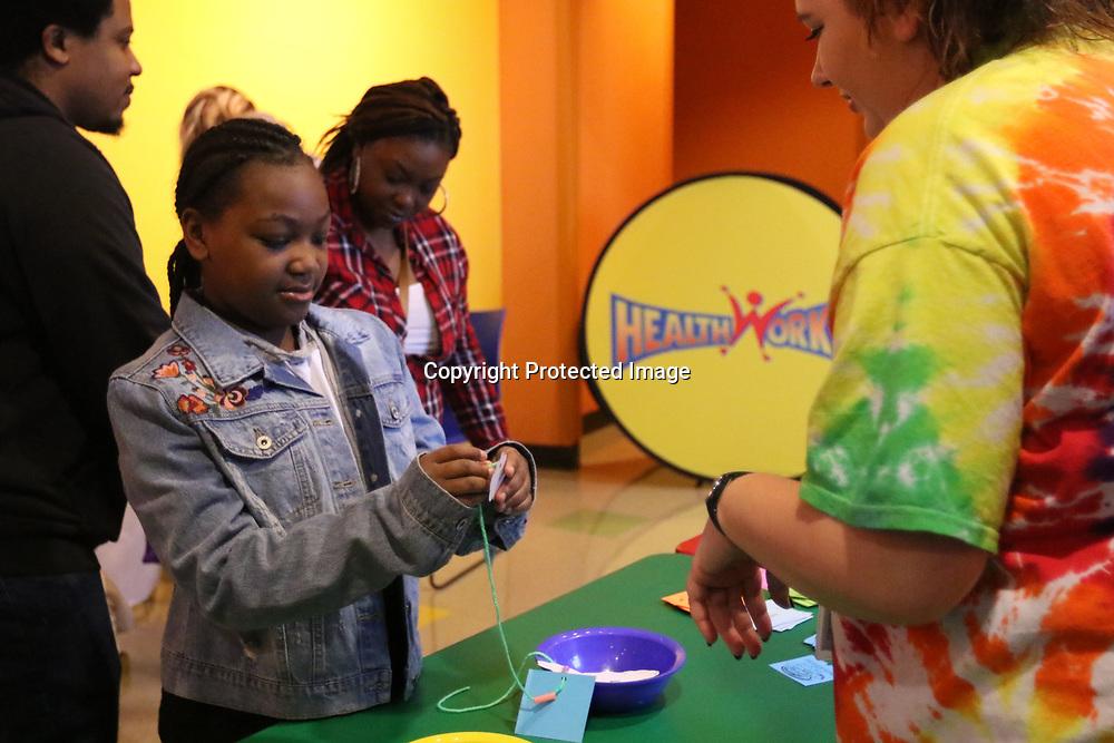 Baylee Hallmark,right, helps Ke'Asia Standifer, 11, make a Healthworks necklace Saturday at Healthwork's 9th Birthday celebration