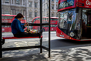 A woman waits for a bus with feet tucked under the hand support rail in Whitehall, on 9th May 2018, in London, England.