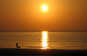 Man walking his dog at sunrise on Jekyll Island Beach.