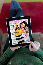 Woman using iPad tablet computer to read Cosmopolitan magazine online edition
