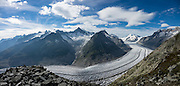 See the vast Aletsch Glacier from atop the Eggishorn in Valais canton of Switzerland, the Alps, Europe. From Fiesch, ascend via cable car first to see stunning views from the Eggishorn (2926 m), then return to the mid station of Fiesheralp, from where you can hike a spectacular ridge above Aletsch Glacier via Hohbalm, Moosfluh, Hohfluh, Riderfurke, and Riederalp. Grosser Aletschgletscher is the largest glacier in the Alps (23 km or 14 miles long in 2014). The Swiss Alps Jungfrau-Aletsch region is honored as a UNESCO World Heritage Site. This image was stitched from multiple overlapping photos.