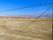 Israel, Dead Sea. Abandoned barracks buildings on the shore as seen through barbed wire fence