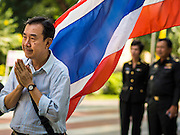 28 NOVEMBER 2014 - BANGKOK, THAILAND:  A man standing in front of a Thai flag at Siriraj Hospital offers birthday prayers for Bhumibol Adulyadej, the King of Thailand. The King was born on December 5, 1927, in Cambridge, Massachusetts. The family was in the United States because his father, Prince Mahidol, was studying Public Health at Harvard University. He has reigned since 1946 and is the world's currently reigning longest serving monarch and the longest serving monarch in Thai history. Bhumibol, who is in poor health, is revered by the Thai people. His birthday is a national holiday and is also celebrated as Father's Day. He is currently hospitalized in Siriraj Hospital, recovering from a series of health setbacks. Thousands of people come to the hospital every day to sign get well cards for the King.      PHOTO BY JACK KURTZ