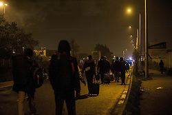 October 24, 2016 - Calais, France - Refugees arriving and waiting at the hangar of distribution of refugees with their luggage. Refugees are leaving the jungle in Calais, France on october 24, 2016. The dismantling of the jungle began Monday morning. Refugees come accompanied by the associations to the starting center ''C.A.O.''. Police frames the device. More than 850 press credentials were distributed. (Credit Image: © Julien Pitinome/NurPhoto via ZUMA Press)