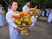 19 JULY 2014 - KHLONG LUANG, PATHUM THANI, THAILAND: A woman carries the robes for a monk she is sponsoring during an ordination at Wat Phra Dhammakaya. Seventy-seven men from 18 countries were ordained as Buddhist monks and novices at Wat Phra Dhammakaya, a Buddhist temple  north of Bangkok, Saturday. It is the center of the Dhammakaya Movement, a Buddhist sect founded in the 1970s and led by Phra Dhammachayo (Phrathepyanmahamuni). It is the largest temple in Thailand. The Dhammakaya sect has an active outreach program that attracts visitors from around the world.    PHOTO BY JACK KURTZ