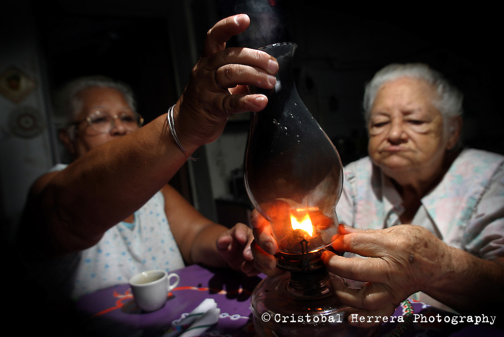 Mercedes Benitez, left, helps her mother Zenaida to turn on a kerosene lamp during a blackout in their neighbourhood on Friday October 1st. 2004 in Havana, Cuba. Cuban government planned this blackout like measures to combat severe problems in the country's electrical system. (Photo/Cristobal Herrera)