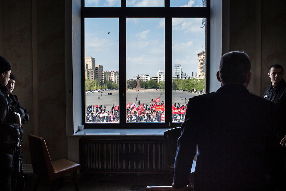 KHARKIV, UKRAINE - APRIL 24: Police watch pro-Russian separatists holding a rally outside from a window in the regional administration building on April 24, 2014 in Kharkiv, Ukraine. The legislative body for the Kharkiv region, which was holding a session, was urged by pro-Russian protesters to schedule a referendum on greater autonomy from the central government in Kiev. (Photo by Brendan Hoffman/Getty Images) *** Local Caption ***