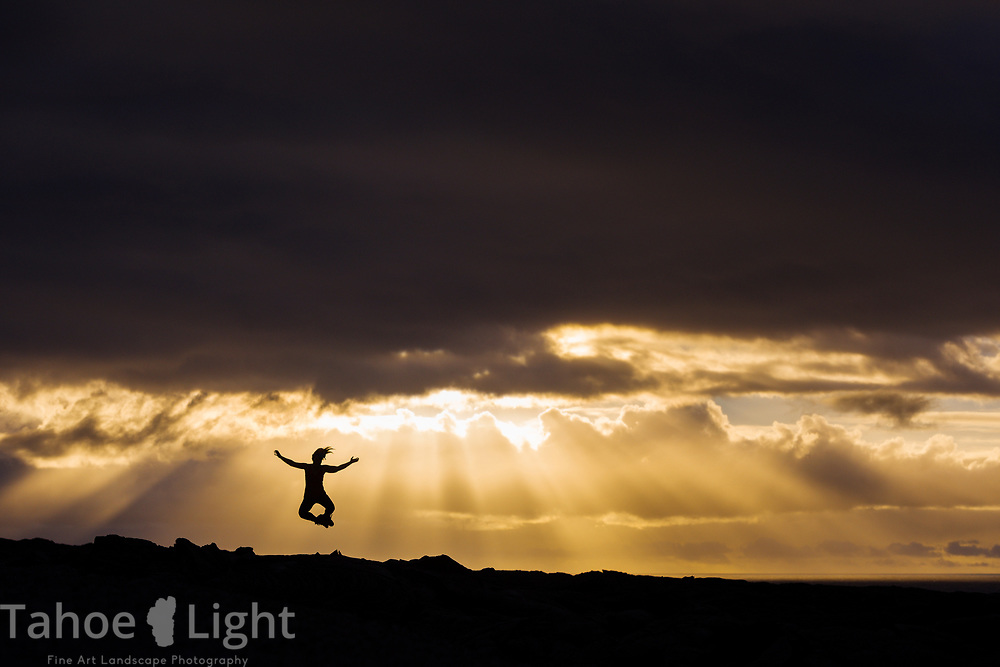 Woman jumping in the air and clicking heels together during dramatic sunset