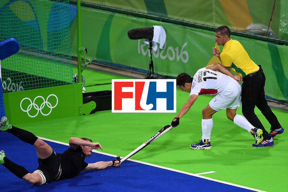 Belgium's Thomas Briels (C) crashes into a referee during the mens's field hockey Belgium vs New Zealand match of the Rio 2016 Olympics Games at the Olympic Hockey Centre in Rio de Janeiro on August, 12 2016. / AFP / MANAN VATSYAYANA        (Photo credit should read MANAN VATSYAYANA/AFP/Getty Images)