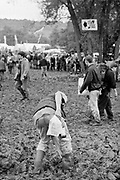 An individual attempts to release welly from mud , in the background is a large crowd of people. Glastonbury 1997