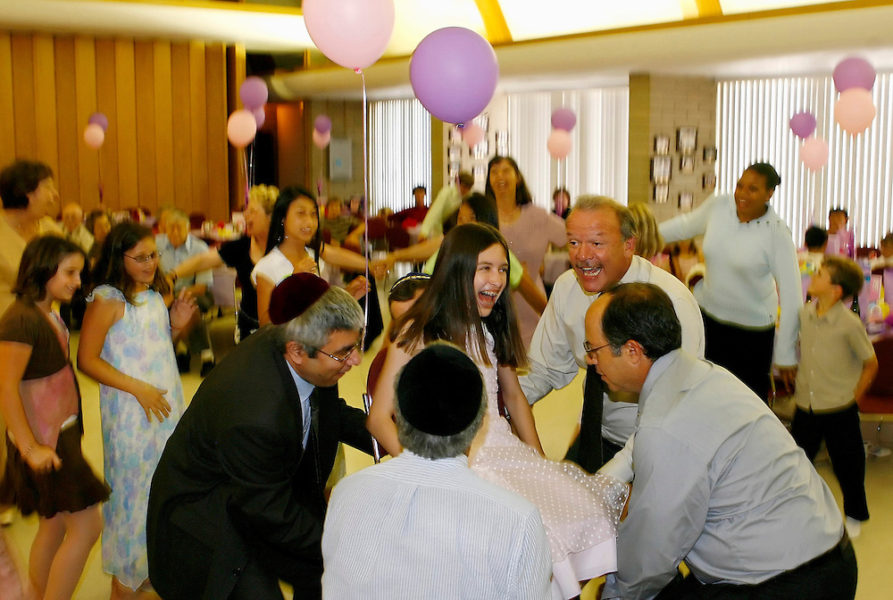 Hannah reacts as she is hoisted up on a chair while guests dance around her during a luncheon celebration for her bat mitzvah.