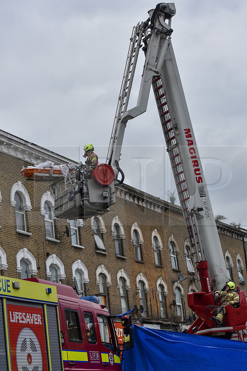 © Licensed to London News Pictures. 01/04/2020. London, UK. A patient is lowered to the ground at an incident involving all emergency services where a suspected COVID-19 case was isolated and removed from their home. Uxbridge Road in Shepherd's Bush was closed for an hour as ambulance, fire brigade and police attended, extracting the patient by crane from a three story apartment building in West London. PPE (personal protective equipment) was in evidence, with the fire brigade using full face respirators normally reserved for firefighting. A police officer commented the Metropolitan police force are issued only with rubber gloves. Ambulance workers decontaminated the scene and reusable equipment before moving on.  Photo credit: Guilhem Baker/LNP