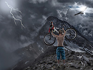 Photo manipulation of mountain biker raising his bike in defiance of the mountain. A vulture circles overhead whilst another sits on the ground watching. The biker image is mine below credits to stock image providers.<br /> Vulture flying loopyker stock<br /> Dramatic weather Burtyn<br /> Whiteback vulture Salaolastock.<br /> Brushes PSDbox A studio photoshoot of sports people Images by Durban portrait and lifestyle photographer Paul Gregg for Imagemakers.