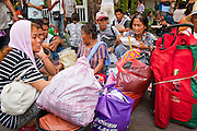 20 MAY 2010 - BANGKOK, THAILAND: People wait to be evacuated from Royal Thai police headquarters in the Ratchaprasong Intersection in Bangkok Thursday. The people were among the thousands who took shelter in Wat Pathumwanaram, across the street from the police headquarters, during heavy fighting between anti government protesters and the army on Wednesday. The day after a military crackdown killed at least six people, Thai authorities continued mopping up operations around the site of the Red Shirt rally stage and battle fires set by Red Shirt supporters in the luxury malls around the intersection. PHOTO BY JACK KURTZ