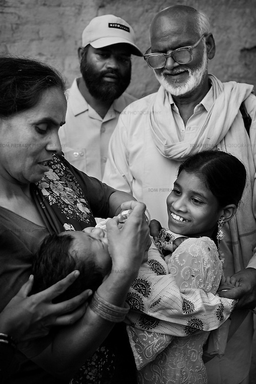 A Unicef coordinator vaccinates a child in Bilari town, close to Moradabad city. She is accompanied by local Doctor Talib (in white cap). Doctors and community influencers including teachers and religious leaders have been identified by Unicef as integral to encouraging the participation of all in the polio vaccination effort. ..India is one of only four countries in the world reported to suffer endemic polio. Only 66 new cases of the disease were reported in India in 2005. But in 2006 that figure leapt ten-fold. In September, UN Secretary General Kofi Annan wrote to Indian Prime Minister Manmohan Singh expressing concern at the new polio outbreak. The Indian government, together with partners including Unicef and Rotary International has embarked on a renewed effort to eradicate polio. Overcrowded areas of poor sanitation are particularly susceptible to the virus. Focusing on the poor north Indian states of Uttar Pradesh and Bihar which between them are home to more than 250 million people, Unicef is coordinating the largest public health drive in the world. The task is to vaccinate all children under the age of five during a series of vaccination rounds. Unicef has mobilised thousands of volunteers to administer and supervise the vaccination effort. Unicef has also recruited people with influence to encourage communities to have their children protected against polio. Misinformation, rumours and a frustration with the lack of other health services mean that many households, particularly in Muslim areas, resist vaccination. ..Photo: Tom Pietrasik.Moradabad District, Uttar Pradesh, India..November 13th 2006