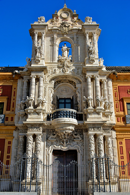 Entrance of San Telmo Palace in Mar&iacute;a Luisa Park in Seville, Spain<br /> The entrance of San Telmo Palace deserves inspection. This spectacular portal was created by the son and grandson of the building&rsquo;s main architect, Leonardo De Figueroa. He died 24 years before this entry was finished in 1754. The upper balcony is flanked by twelve female sculptures and two atlantes (supporting columns shaped as a man). This flamboyant, ornamental style is called Churrigueresque, named after architect Jos&eacute; Benito de Churriguera. He perfected this form of Spanish Baroque architecture during the early 18th century.