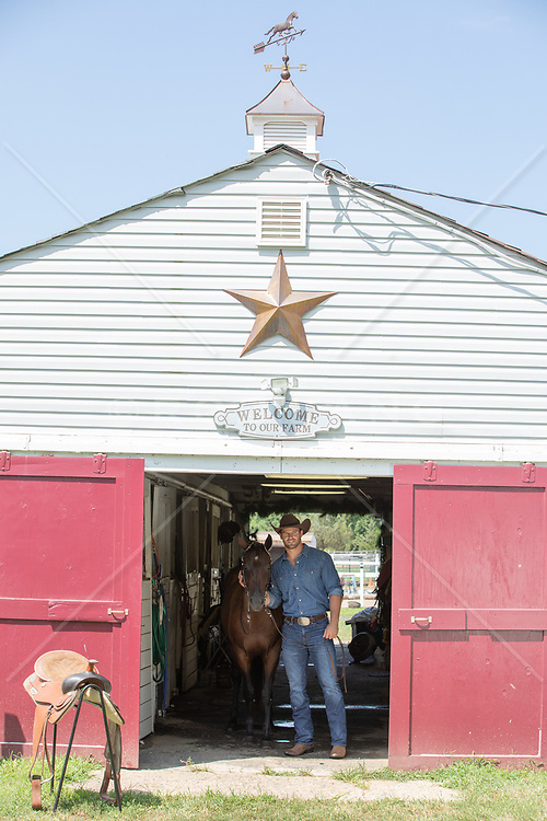 cowboy with his horse in a barn