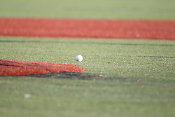 24 July 2015:  A single baseball lies on the artificial turn near the pitchers mound during a Frontier League Baseball game between the Gateway Grizzlies and the Normal CornBelters at Corn Crib Stadium on the campus of Heartland Community College in Normal Illinois