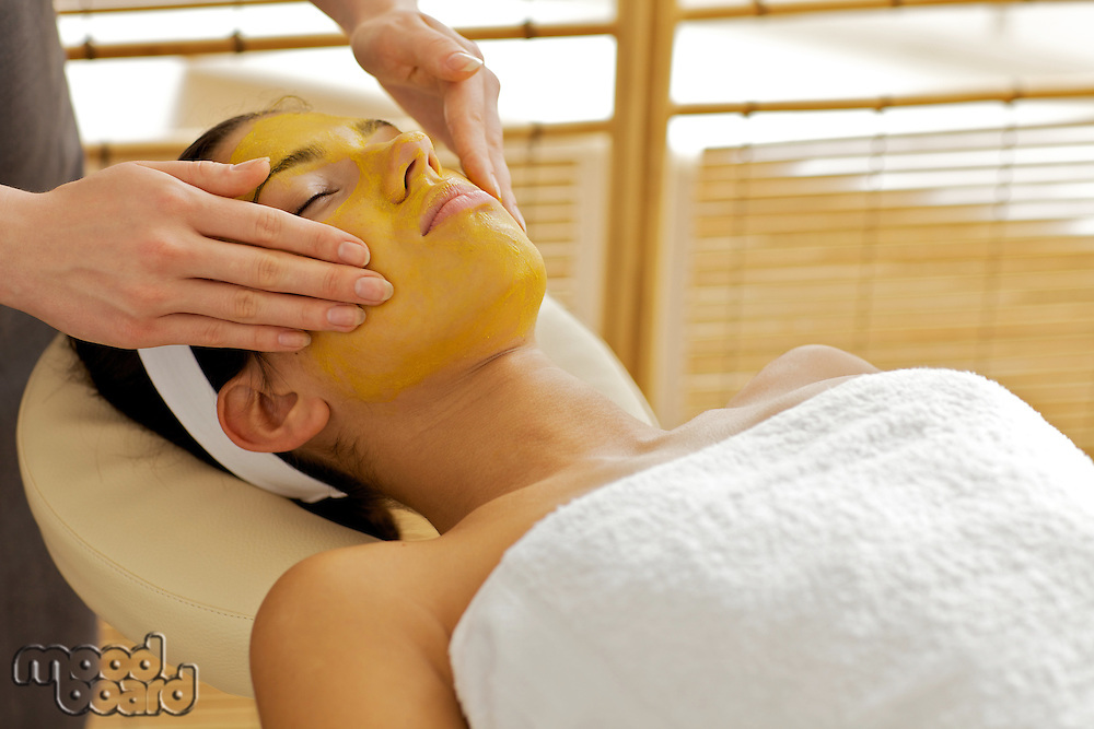 Young woman receiving facial treatment in spa