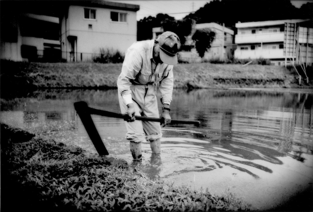 """83 year old farmer slowly reinforces walls of rice paddy what in his lifetime has become a farm swallowed by the capital's western suburbs, where  the average age of farmers hovers around 60 years, Naganuma, Tokyo, Japan.  When asked whether his son continues farming, he responded that his son has a """"money job"""".   Financial incentives have steadily drawn the younger generations of Japanese away from the rural life."""