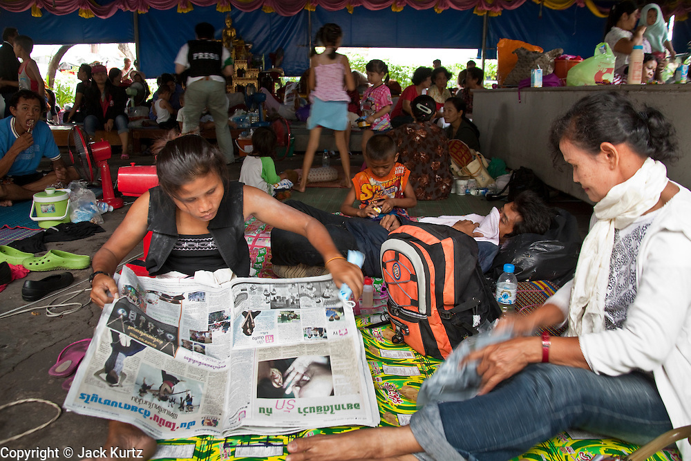 "17 MAY 2010 - BANGKOK, THAILAND: A woman reads a Thai newspaper in Wat Pathumwanaram Monday. More than 800 people, mostly women and children, have gathered at Wat Pathumwanaram, near the Red Shirt protest area, hoping the Thai army will not attack them in the temple. The official start of the crackdown is expected to start about 15.00 Bangkok time Monday. The Thai government announced Monday that the Red Shirts unofficial military commander and staunch supporter, Thai Army Maj. Gen. KHATTIYA ""Seh Daeng"" SAWASDIPOL, died Monday from wounds he suffered when a sniper shot him in the head on May 12 while he was being interviewed by an American reporter. When the announcement was read to the Red Shirt protesters still camped out in Ratchaprasong intersection in Bangkok many started weeping.   PHOTO BY JACK KURTZ"