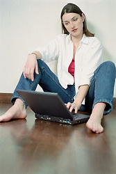 Dec. 05, 2012 - Woman with laptop sitting on floor (Credit Image: © Image Source/ZUMAPRESS.com)