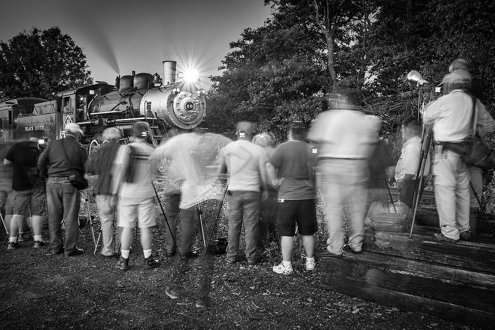 At a 'night photo' session, photographers line up and create a wall that pens the train in.