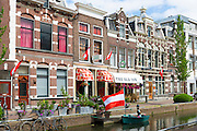 Canalside street with bar, boat and bicycles  in Amsterdam, Holland, The Netherlands