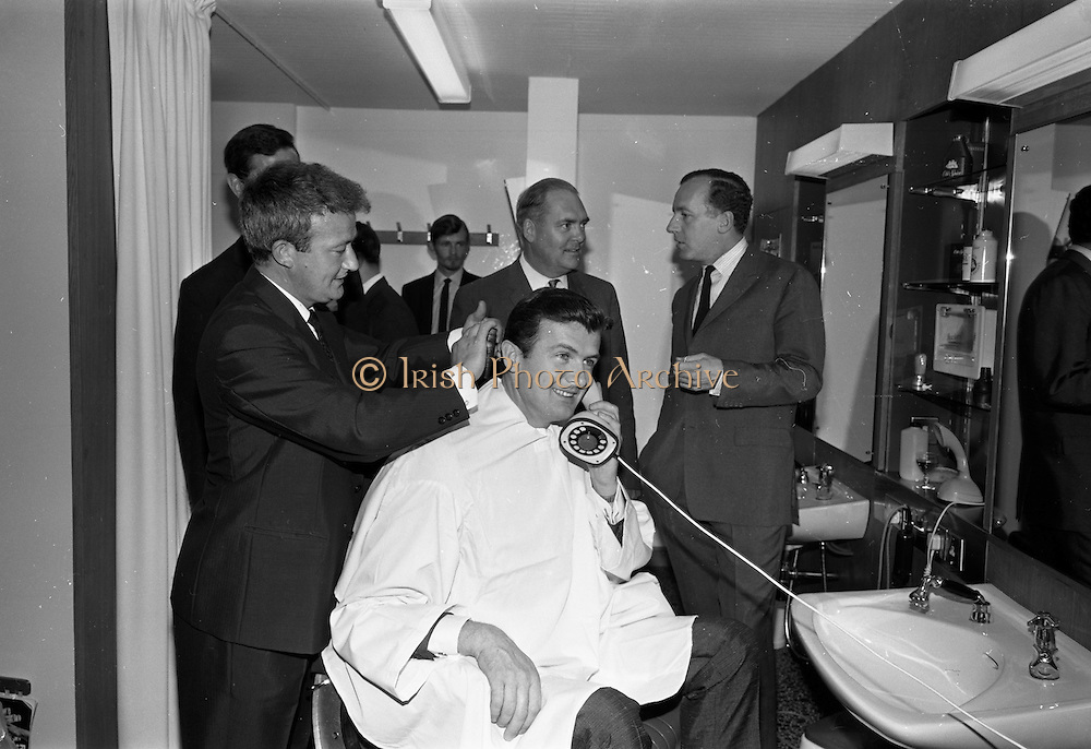 17/07/1967<br /> 07/17/1967<br /> 17 July 1967<br /> Opening of new men's salon at Brown Thomas, Grafton Street, Dublin. Brendan O'Reilly, the TV personality opened a new Mens Department in Brown Thomas and Co. Ltd.. In the new department was a hairdressing salon where while getting your hair done it was possible to make phone calls from the chair. Image shows Brendan o'Reilly being attended to by Tony Byrne, who is in charge of the Hairdressing Salon with Senator E. Rooney (behind O'Reilly) and Mr. John McGuire (extreme right) Managing Director, Brown Thomas Group.