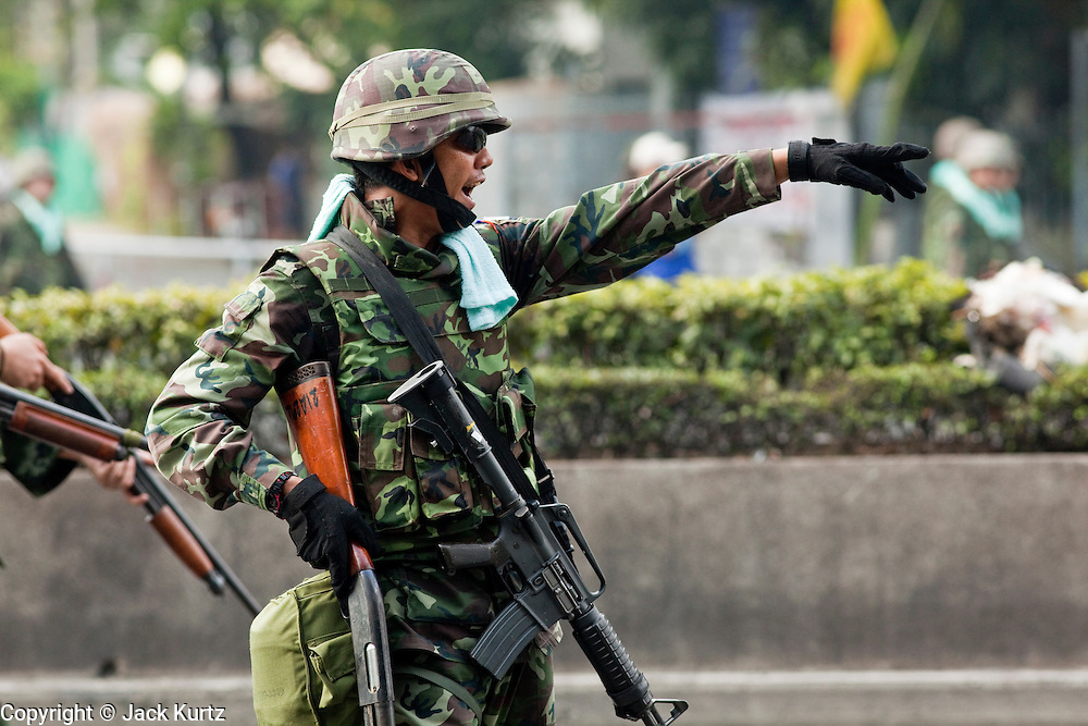 14 MAY 2010 - BANGKOK, THAILAND: A Thai soldier directs others in unit to watch a protester during a street battle in Bangkok Friday. Thai troops and anti government protesters clashed on Rama IV Road Friday afternoon in a series of running battles. Troops fired into the air and at protesters after protesters attacked the troops with rocket and small homemade explosives. Unlike similar confrontations in Bangkok, these protesters were not Red Shirts. Most of the protesters were residents of nearby Khlong Toei slum area, Bangkok's largest slum area. The running battle went on for at least two hours.   PHOTO BY JACK KURTZ