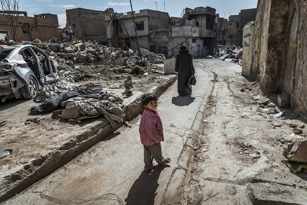 Sawsan, 42, and her daughter walk towards their home in the old quarter of Mosul, which they returned to in February 2018. During the operation to liberate Mosul Sawsan and her family spent 7 months hiding in the basement hiding from  airstrikes and bombardment.