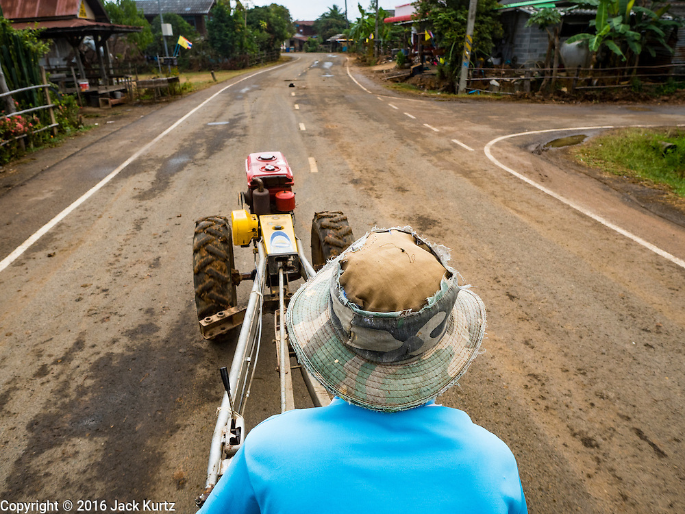 20 JANUARY 2016 - SI LIAM, BURI RAM, THAILAND: A farmer drives his tractor through Si Liam on his way to find water. The drought gripping Thailand was not broken during the rainy season. Because of the Pacific El Nino weather pattern, the rainy season was lighter than usual and many communities in Thailand, especially in northeastern and central Thailand, are still in drought like conditions. Some communities, like Si Liam, in Buri Ram, are running out of water for domestic consumption and residents are traveling miles every day to get water or they buy to from water trucks that occasionally come to the community. The Thai government has told farmers that can't plant a second rice crop (Thai farmers usually get two rice crops a year from their paddies). The government is also considering diverting water from the Mekong and Salaween Rivers, on Thailand's borders to meet domestic needs but Thailand's downstream neighbors object to that because it could leave them short of water.        PHOTO BY JACK KURTZ