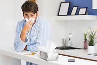 Young ill man blowing nose in tissue paper