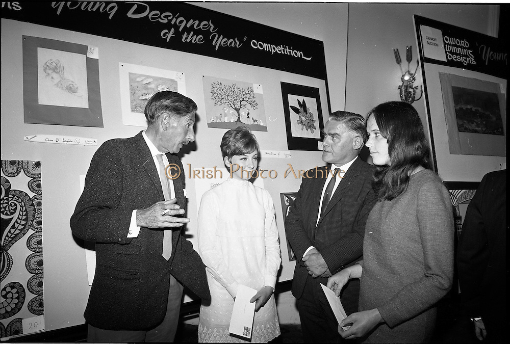 """28/06/1967<br /> 06/28/1967<br /> 28 June 1967<br /> Presentation of prizes at Navan Carpets """"Young Designer of the Year"""" reception in the Royal Hibernian Hotel, Dublin. Left -right are: Mr. Michael Bourke, Principal of the National College of Art; Miss Bronwen Casson, Sandymount, Dublin; Mr. Allan Mallinson, Managing Director, Navan Carpets Ltd. and Miss Claire O'laughlin, Goatstown Road, Dublin, pictured in front of the two ladies designs."""