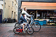 In Utrecht rijdt een vrouw met naast haar een kind op een kinderfiets door de binnenstad.<br /> <br /> In Utrecht cyclists ride at the city center.