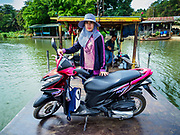 "09 JANUARY 2019 - KANCHANABURI, THAILAND: A passenger on the small ferry that goes across the River Kwai. The ferry goes across the River Kwai downriver from downtown Kanchanaburi, the site of the famous ""Bridge on the River Kwai."" Small ferries like this, once common on Thai river crossings, are disappearing because Thailand has dramatically improved its infrastructure since this ferry started operating about 50 years ago. The ferry operator said his grandfather started the ferry, with a small raft he would pole across the river, in the late 1960s. Now his family has a metal boat with an inboard engine. There are large vehicle bridges across the river about 5 miles north and south of this ferry crossing, but for people in rural communities on the west side of the river the ferry is still the most convenient way to cross the river.      PHOTO BY JACK KURTZ"