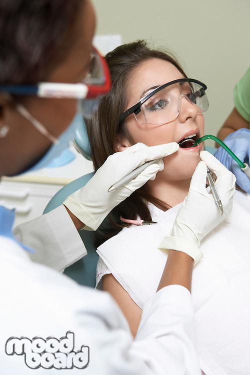 Dentist examining patients teeth in surgery