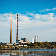 The iconic towers of the Poolbeg Power Station in Dublin, Ireland, reflecting in the waters of Sandyford beach in the foreground