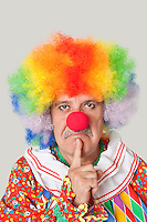 Portrait of angry senior male clown with finger on chin over light gray background