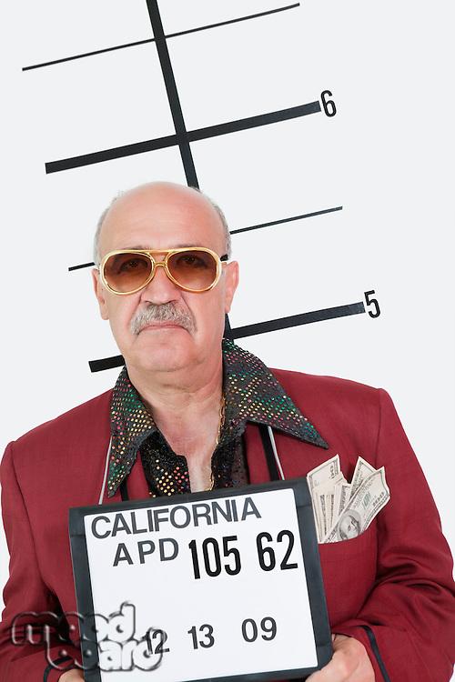 Mug shot of senior man wearing sunglasses and banknotes in pocket