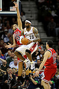 Apr 19, 2010; Cleveland, OH, USA; Cleveland Cavaliers forward LeBron James (23) looks for a pass under pressure from Chicago Bulls center Joakim Noah (13) and guard Kirk Hinrich (12) during the fourth period in game two in the first round of the 2010 NBA playoffs at Quicken Loans Arena. The Cavaliers beat the Bulls 112-102. Mandatory Credit: Jason Miller-US PRESSWIRE