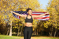 Happy young female holding up American flag in park